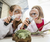 Young scientists with magnifying glasses