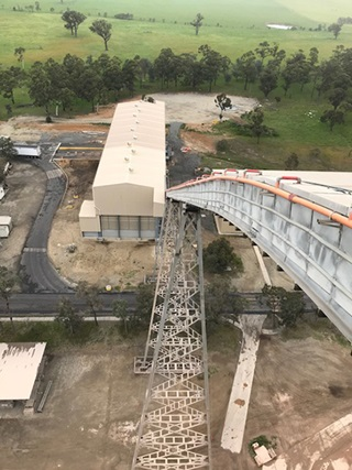 Berrima Cement Works building where trucks deposit their solid waste derived fuels (SWDF) loads, and the encapsulated conveyor which feeds into the kiln's furnace