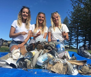 Three girls on a beach with piles of rubbish they have found