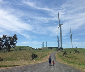 Amy Kean and daughter running along a gravel road in a wind farm