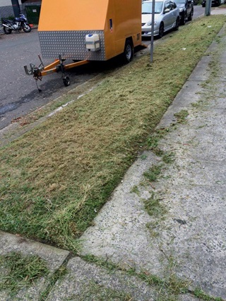 Grass verge with concrete footpath, trailer and parked cars on street.