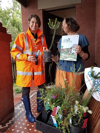 Two women on a front verandah with red brick wall and tessellated tiles, one woman from council in bright orange rain jacket giving native plants to the other who is holding a brochure with Living Connections on the cover.