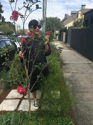 Woman in sunglasses standing in her verge garden next to footpath holding flower of one of her plants.