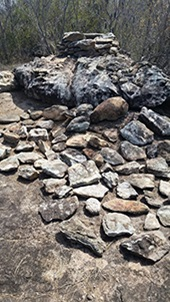 Numerous pieces of sandstone bushrock piled together, with one large rock, to create a sculpture or rock cairn.
