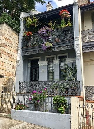 Front view of grey double story terrace house with coloured pot plants hanging from upstairs verandah with a dark grey lacy fence.