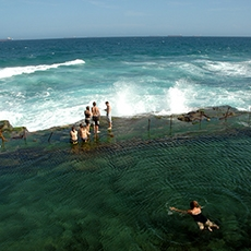 People swimming at the Bogey Hole ocean bath in Newcastle