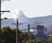 View of Bluescope Steel steelworks from surrounding streets, Port Kembla, with escarpment in the background and steam/pollution rising from one of the stacks