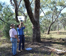Two people stand in bushland holding a 'Blinky Drinker' water container