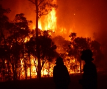 Intense night time high flames fire with NPWS personnel silhouetted Windsor Downs