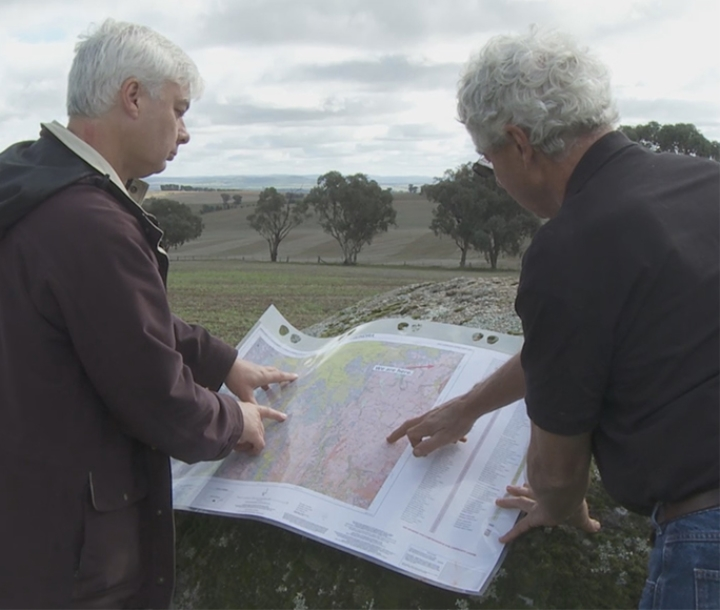 Two men looking at a soil map in the field