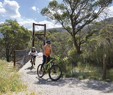 Mountain bikers at the end of a footbridge on the Thredbo Valley Track, Kosciuszko National Park.