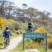 Cyclists passing the Thredbo Valley Track sign, Kosciusko National Park