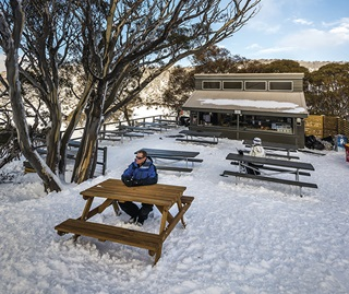 Tourist sitting at an outdoor table at the Alpine Eye cafe, Perisher Valley, in winter