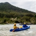 Volunteers paddle their canoe to site infested with weeds, Kosciuszko National Park. Bush regeneration