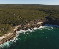Aerial view of the coastline, Royal National Park, with river falling off cliff into the sea