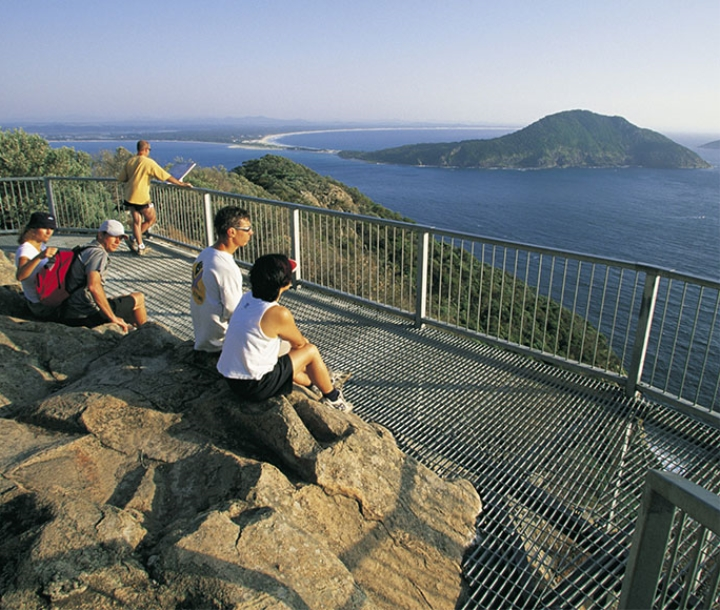 People sitting at Tomaree Head lookout, Tomaree National Park, Port Stephens. Views to Yacaaba Head and Cabbage tree island.