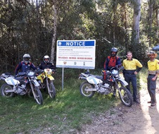 Joint trail bike patrols in Barrington Tops National Park in front of 'No Rego No Ride' sign
