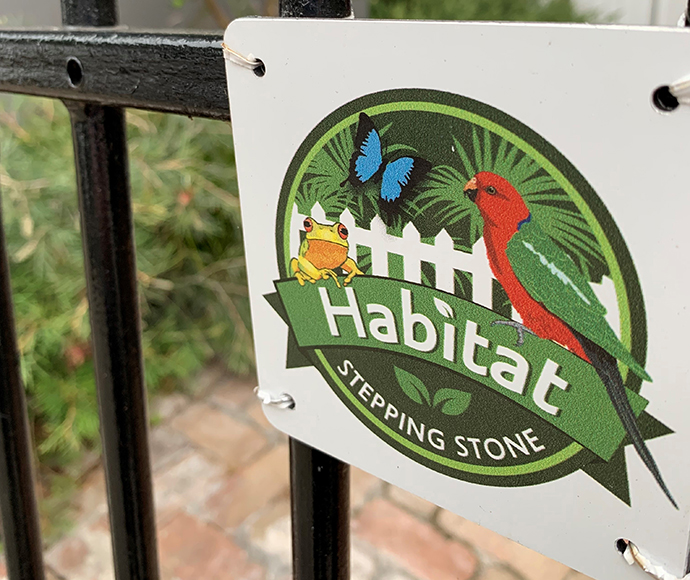 Habitat Stepping Stones plaque attached to black wrought iron fence.